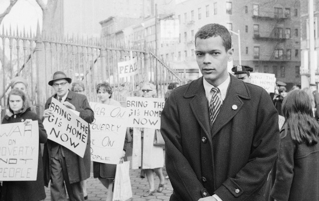Julian Bond of Georgia, 26, watches as people stream into the St. Mark's Church-on-the-Bouwerie to hear him speak in New York, Feb. 10, 1966. His speech came at the end of a peace rally and march which began in midtown. Bond was ousted from Georgia's legislature because of his opposition to the Viet Nam war. He asserted in his speech that his plight has wedded civil rights and anti-Viet Nam War supporters. (AP Photo/Marty Lederhandler)
